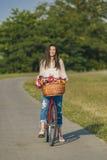 A mulher de sorriso nova monta uma bicicleta Foto de Stock Royalty Free