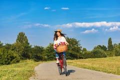 A mulher de sorriso nova monta uma bicicleta no campo Fotos de Stock Royalty Free