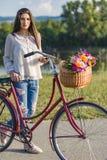 A mulher de sorriso nova monta uma bicicleta no campo Imagens de Stock Royalty Free