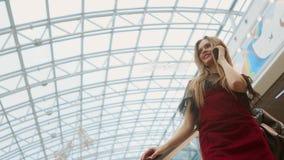 Mulher de sorriso nova na posição azul do t-shirt no shopping usando o smartphone, consultando, lendo a notícia, conversando com filme