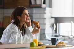 A mulher de sorriso nova no roupão apenas levantou-se na manhã na cozinha usando o telefone esperto imagens de stock royalty free