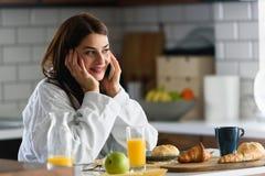 A mulher de sorriso nova no roupão apenas levantou-se na manhã na cozinha usando o telefone esperto fotografia de stock