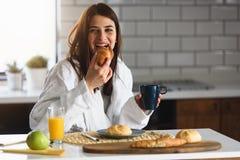 A mulher de sorriso nova no roupão apenas levantou-se na manhã que come o café da manhã na cozinha fotos de stock