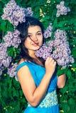 Mulher de sorriso nova nos arbustos lilás Foto de Stock