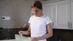 A mulher de sorriso nova prepara ingredientes de mistura da massa o na bacia usando o batedor de ovos na cozinha Alimento caseiro video estoque