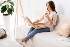 mulher de sorriso nova que come a pizza ao descansar no sofá fotografia de stock royalty free