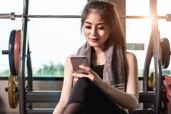 Mulher de sorriso nova que escuta a música no smartphone no gym Imagens de Stock