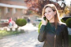 Mulher de sorriso nova que fala no telefone celular Fotografia de Stock Royalty Free