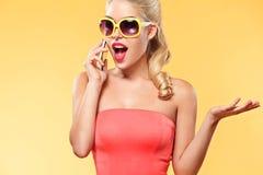 Mulher de sorriso nova que fala pelo telefone celular sobre a venda em sexta-feira preta Menina com espaço amarelo do fundo e da  foto de stock royalty free