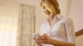 Mulher de sorriso nova que guarda um smartphone e que datilografa nele filme