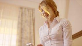 Mulher de sorriso nova que guarda um smartphone e que datilografa nele video estoque
