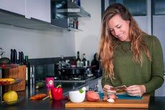 Mulher de sorriso nova que lê a receita na cozinha imagens de stock royalty free