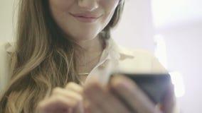 Mulher de sorriso nova que mantém um smartphone disponivel e que surfa no Internet