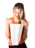 Mulher de sorriso nova que olha no saco de compra Fotografia de Stock
