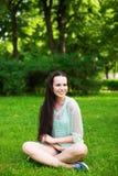 Mulher de sorriso nova que senta-se na grama imagem de stock