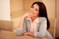 Mulher de sorriso nova que senta-se na tabela Imagens de Stock