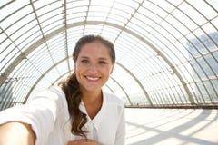 Mulher de sorriso nova que toma o selfie no estação de caminhos-de-ferro imagem de stock royalty free