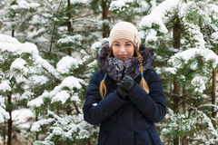 A mulher de sorriso nova que veste a guarnição real encapuçado azul da pele reveste para baixo a apreciação da vista na floresta  fotografia de stock royalty free