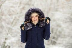 A mulher de sorriso nova que veste a guarnição real encapuçado azul da pele reveste para baixo a apreciação da vista na floresta  fotografia de stock