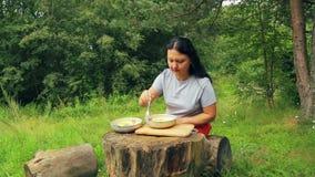 A mulher de sorriso nova senta-se em um coto na borda de uma floresta e corta-se fatias de pêssego para a salada em uma placa de  video estoque