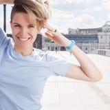 Mulher de sorriso nova sobre a ponte no fundo da arquitetura da cidade foto de stock royalty free