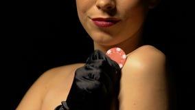 Mulher de sorriso que afaga o corpo, mostrando a microplaqueta de pôquer na câmera, jogos do casino video estoque