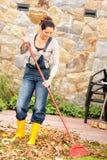 Mulher de sorriso que ajunta o jardim dos trabalhos domésticos da queda das folhas Fotografia de Stock