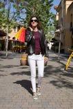 Mulher de sorriso que anda com os sacos de compras na rua Imagens de Stock Royalty Free