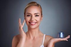 Mulher de sorriso que aplica o creme na cara Fotografia de Stock