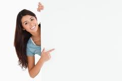 Mulher de sorriso que aponta em uma placa fotografia de stock royalty free