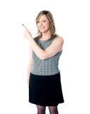 Mulher de sorriso que aponta para a área de espaço da cópia Imagens de Stock