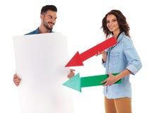 A mulher de sorriso que aponta setas à placa vazia guardou pelo homem Imagem de Stock Royalty Free