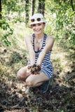 Mulher de sorriso que aprecia os cones do pinho na floresta no verão Imagem de Stock