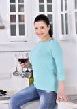 Mulher de sorriso que aprecia a videira vermelha na cozinha Foto de Stock