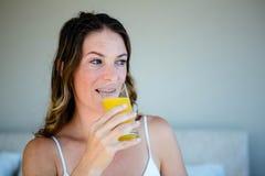 mulher de sorriso que bebe um vidro do suco de laranja imagem de stock royalty free