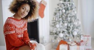 Mulher de sorriso que bebe uma caneca de café do Natal Imagens de Stock