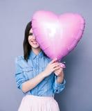 A mulher de sorriso que cobre seu olho com o coração deu forma ao balão Fotos de Stock Royalty Free