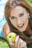Mulher de sorriso que come Apple com dentes perfeitos Fotos de Stock Royalty Free