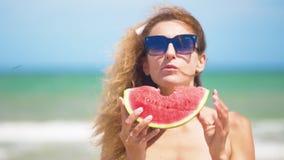 Mulher de sorriso que come a melancia na praia Mulher que come o fruto saboroso do verão Tempo de ver?o feliz filme