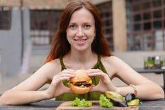 Mulher de sorriso que come o cheeseburger fora Fotografia de Stock