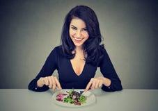 Mulher de sorriso que come a salada saudável imagem de stock royalty free