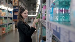 Mulher de sorriso que compra uma garrafa da água na seção do supermercado, compra do mantimento da mulher de negócios Fotos de Stock Royalty Free