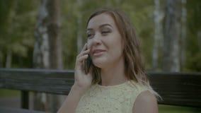 Mulher de sorriso que conversa no telefone celular no banco video estoque