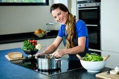 mulher de sorriso que cozinha na parte superior do fogão fotografia de stock royalty free