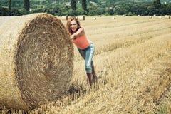 Mulher de sorriso que empurra o monte de feno e ter o divertimento pela colheita Fotos de Stock Royalty Free
