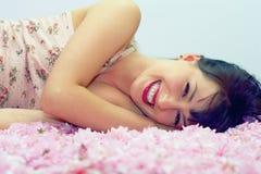 Mulher de sorriso que encontra-se nas pétalas da flor Fotografia de Stock