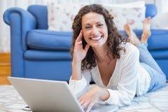 Mulher de sorriso que encontra-se no assoalho e em usar seu portátil Foto de Stock
