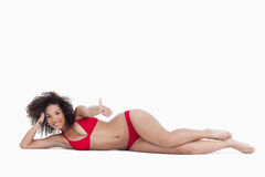 Mulher de sorriso que encontra-se para baixo ao colocar seus polegares acima Imagem de Stock Royalty Free