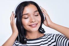 Mulher de sorriso que escuta a música nos fones de ouvido com os olhos fechados Imagens de Stock Royalty Free