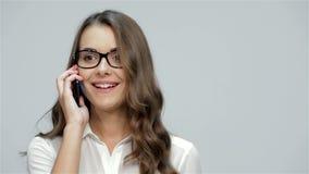 Mulher de sorriso que fala no telefone celular video estoque